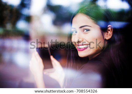 A beautiful young Indian woman smiling and looking through a glass window while holding a phone with blank screen in her hands