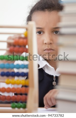 A beautiful young mixed race African American girl reading in a school classroom with a pile of books in front of her using an abacus