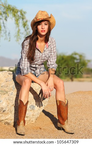 A beautiful young model in a western themed outfit poses in the desert