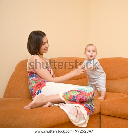 A beautiful young mother wearing a dress with flowers and a charming kid on the orange sofa. Baby learning to stand