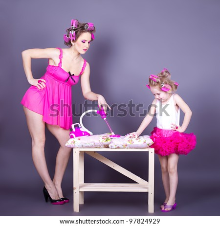 A beautiful young mother with her daughter in the form of cheerful housewives. Studio shot on a gray background.