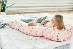 A beautiful young mother with long blonde hair and a daughter of 2-3 months are resting on the bed with pink pillow in the bedroom. Happiness is in children. The long-awaited baby
