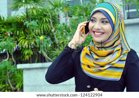 A beautiful young muslim girl executive talking on the phone happily