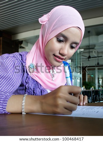 A beautiful young muslim woman filing out a form.
