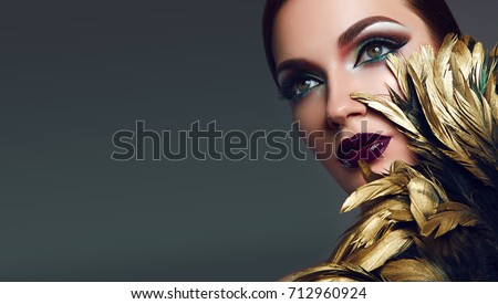 A beautiful young sexy girl with bright makeup covers part of her face with golden shiny feathers. masquerade, accessories.