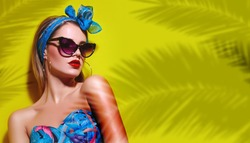 A beautiful young tanned girl with a headscarf on her head and wearing sunglasses stands near a yellow wall in the south. Fashionable blue summer dress, bright make-up, tan. Palms, shadow.