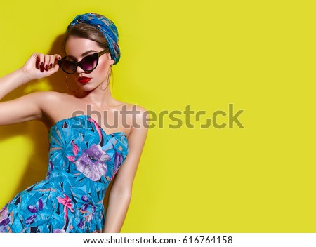 A beautiful young tanned girl with a headscarf on her head and wearing sunglasses stands near a yellow wall in the south. Fashionable blue summer dress, bright make-up, tan.