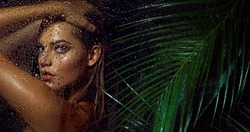 A beautiful, young, tanned girl with wet hair and wet skin is standing in the jungle in the rain.Beauty, fashion, cosmetology, natural, nature, natural, spa, detox, plants.