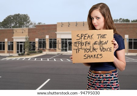A beautiful young teenage woman holding up a sign