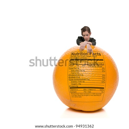 A beautiful young teenage woman standing behind an orange with a nutrition label