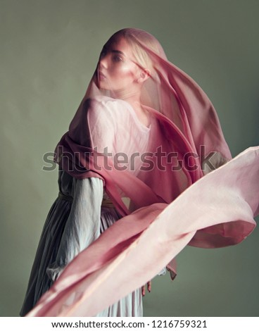 A beautiful young tender girl in a chiffon dress is covered with a drapery made of thin fabric that develops in the wind.fashion, beauty, makeup, cosmetics, beauty salon, style, personal care.
