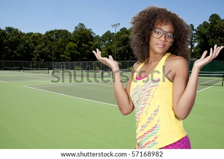 A beautiful young woman at a tennis court