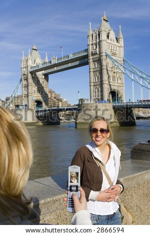 A beautiful young woman bathed in summer sunshine has her picture taken on a camera phone in front of Tower Bridge, London, England