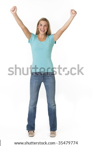 A beautiful young woman cheering with her fists in the air.  She is smiling excitedly and is looking directly at the camera. Vertically framed shot.