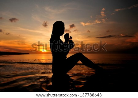 a beautiful young woman drinking cocktail on the beach at sunset on background