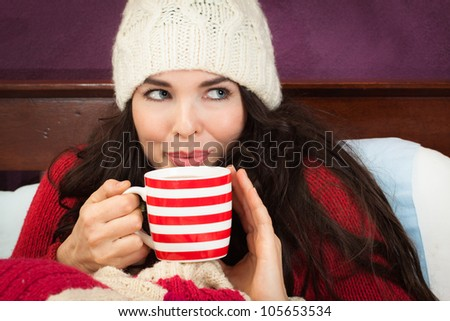 A beautiful young woman enjoying a hot drink under the blankets in bed.