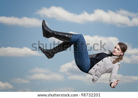 A beautiful young woman falling through the sky - stock photo