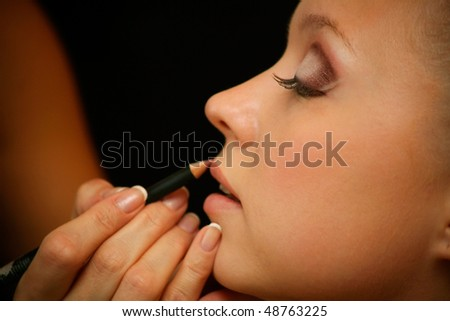A beautiful young woman having the final touches applied to her make up by a beautician