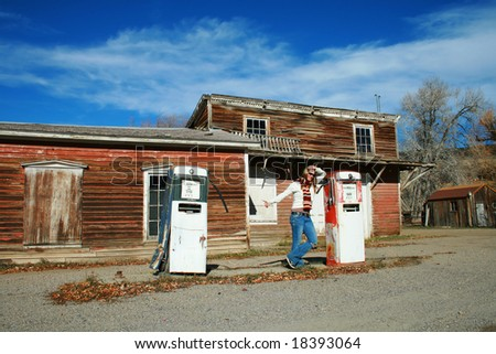 A beautiful young woman hitch hiking from a deserted gas station