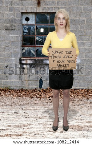 A beautiful young woman holding up an inspirational sign