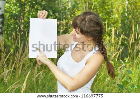 a beautiful young woman holds a blank white sheet of paper