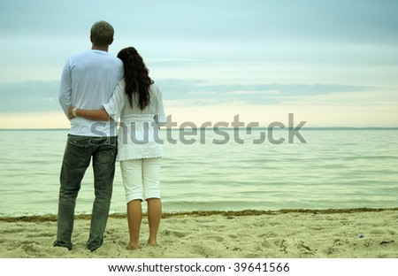 A beautiful young woman holds her handsome partner as they watch the sunset together on a romantic beach.