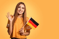 A beautiful young woman holds in her hands the flag of Germany and shows the OK sign. Exchange student, learn Germanic language. Tourist traveling. Yellow, orange background. Football fan.