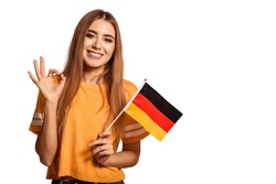 A beautiful young woman holds in her hands the flag of Germany and shows the OK sign. Exchange student, learn Germanic language. Tourist traveling. White background. Isolate. Football fan.