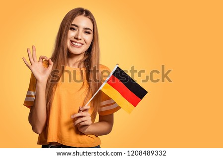 A beautiful young woman holds in her hands the flag of Germany and shows the OK sign. Exchange student, learn Germanic language. Tourist traveling. Yellow, orange background. Football fan. Foto d'archivio ©