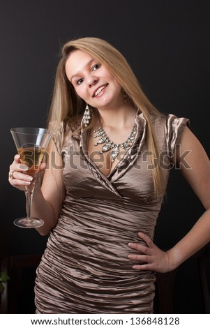 A beautiful young woman in an elegant gown looks at the camera holding up a champagne glass to toast a celebration