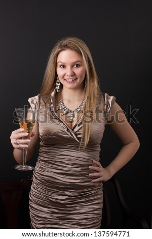 A beautiful young woman in an elegant gown looks at the camera holds up a champagne glass to toast a celebration
