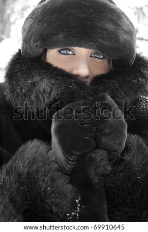 A beautiful young woman in faux fur coat and hat outdoors in winter on a light snowy day.