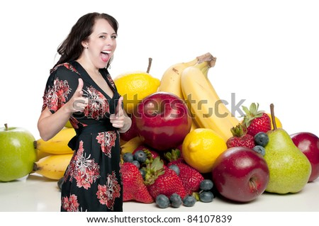 A beautiful young woman in front of a wide assortment of delicious and fresh fruits - stock photo