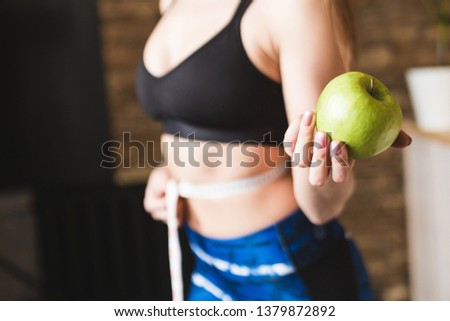A beautiful young woman in sportswear measures the measured flight waist circumference and holds an apple in one hand. Sport, diet and weight loss