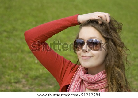 A beautiful young woman in sunglasses relaxing in the park on a bench. Straightens his hair.