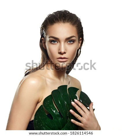 A beautiful young woman in the studio on a white background with wet skin and wet hair holds a large green tropical leaf in her hands and covers a part of her body. Natural cosmetics, natural beauty.