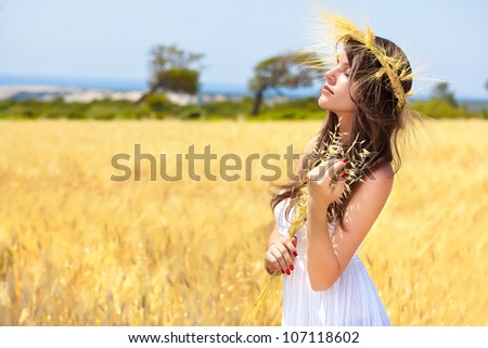 A beautiful young woman is in the field with a wreath