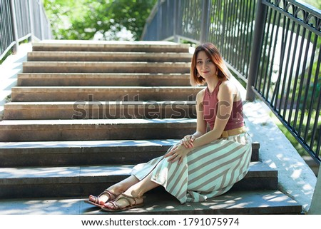 A beautiful young woman is sitting on the steps of a bridge on a summer day.