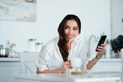 a beautiful young woman is using an application in her smart phone device while enjoying a cup of coffee, sitting at a kitchen table