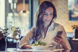 A beautiful young woman is using an application to send an sms message in her smartphone device while eating a salad at the restaurant