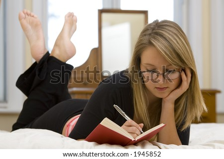 A beautiful young woman laying on her bed writes personal thoughts in her diary