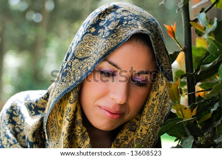 A beautiful young woman meditating in garden wearing a traditional cape