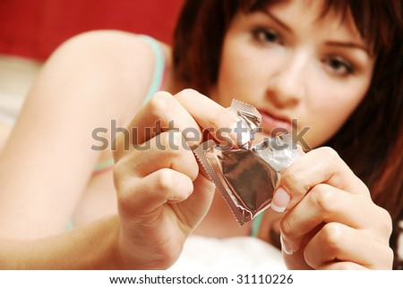 A beautiful young woman opening a condom on her bed. Focus on the condom in the foreground.