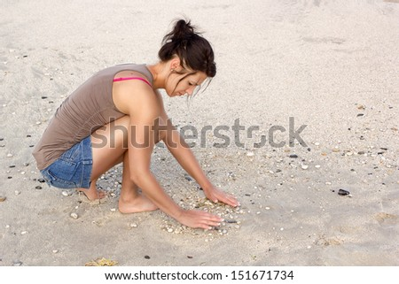 A beautiful young woman playing on beach sand with pebbles.