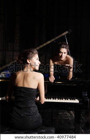 A beautiful young woman playing piano with her twin on the piano