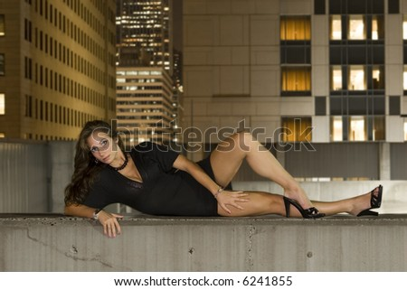 A beautiful young woman posing on the roof of a parking garage.