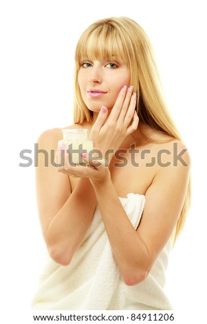 A beautiful young woman putting cream on her skin