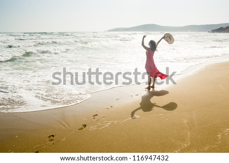 A beautiful young woman raises her arms towards the sea