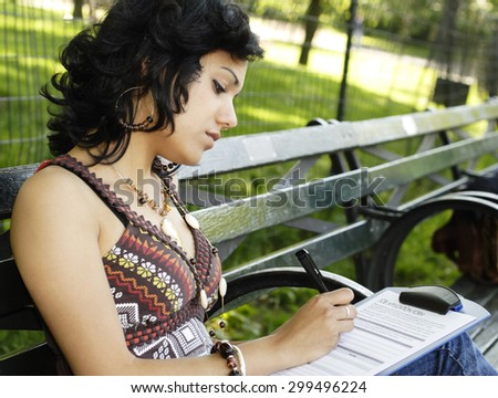A beautiful young woman seated on a park bench filling out a job application.