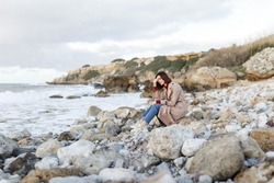 A beautiful young woman sits on a rocky shore and thinks about something. Evening portrait of a beautiful young woman in nature. Solitude, retreat, isoloation, seclusion concept